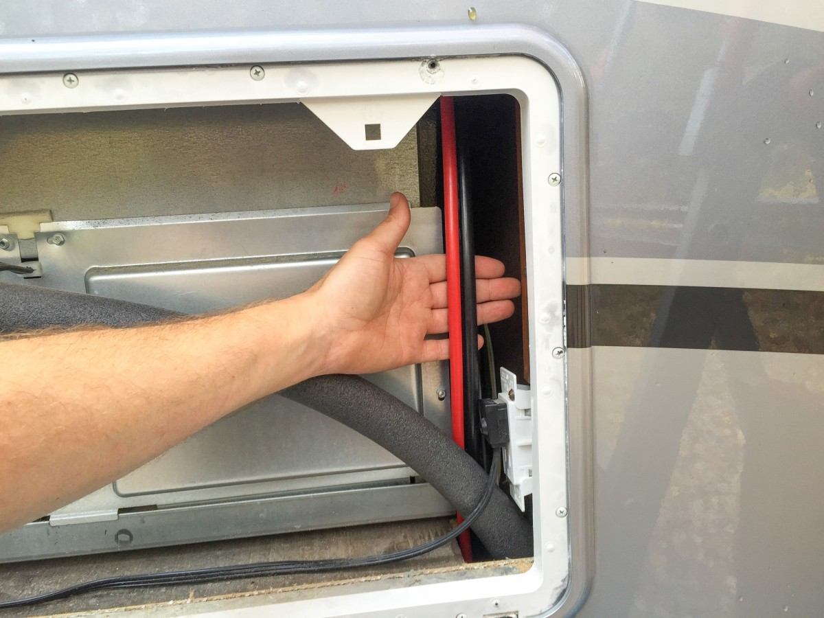 Grabbing the solar wire via the refrigerator access panel outside the RV.